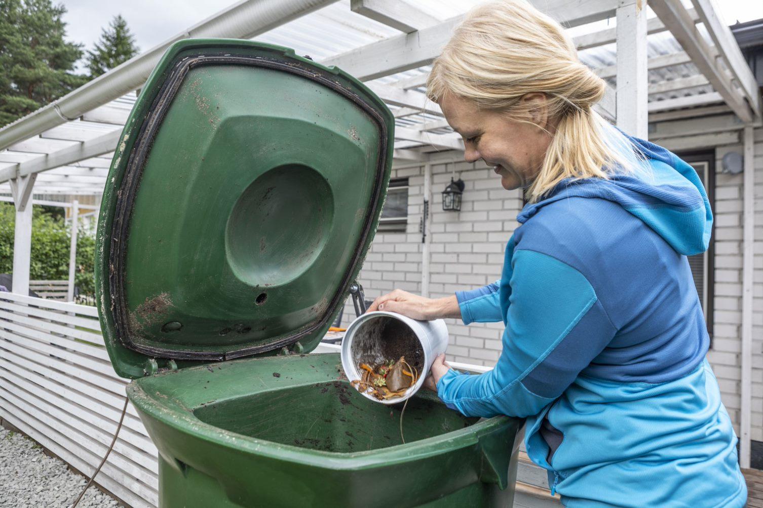 Asukas kaataa biojätettä kompostoriin biojäteastiasta